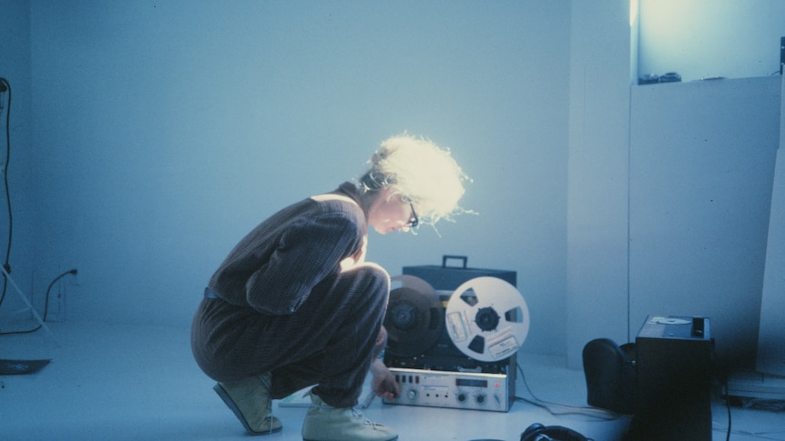 Photo of woman with light hair tied up, crouching over transistor in bare room with bluish light.