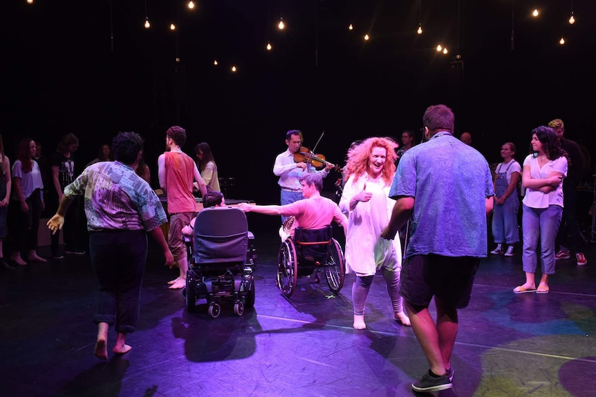 Group of people on stage, including two wheelchair users, someone who appears to be singing.