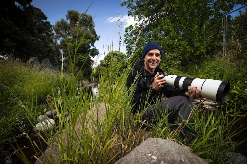 A man with a camera and a large lens sits on a river bank.