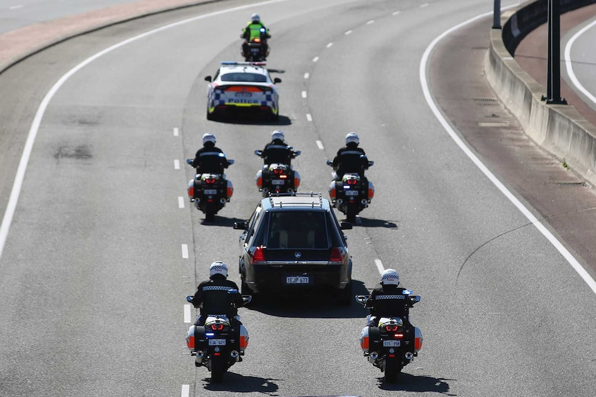 A hearse surrounded by police cars and motorbikes drives down a freeway.