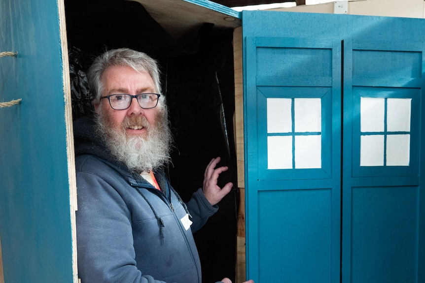 A man stands inside an upright blue coffin designed to look like Dr Who's tardis