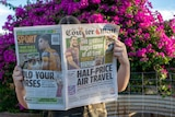 A woman holds up a newspaper in front of her face in front of a bush of pink flowers.
