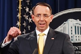 Rod Rosenstein - great name - makes a gesture with his hand as he speaks to media at a lectern