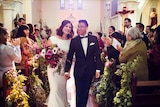 A bride and groom walking down the aisle at an unplugged wedding held in a Catholic church.