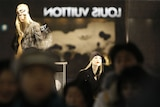 Passersby walk past a display window as the logo of Louis Vuitton is reflected on it