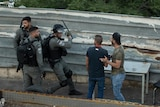 An Israeli border police officer prepares to hit a Palestinian man.
