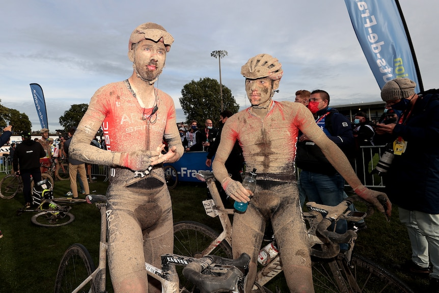 Amaury Capiot and Connor Swift sit on their bikes while covered in mud and sweat