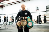 A man holding three boxing title belts.