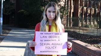 A student holds a sign campaigning for action on campus sexual assault.