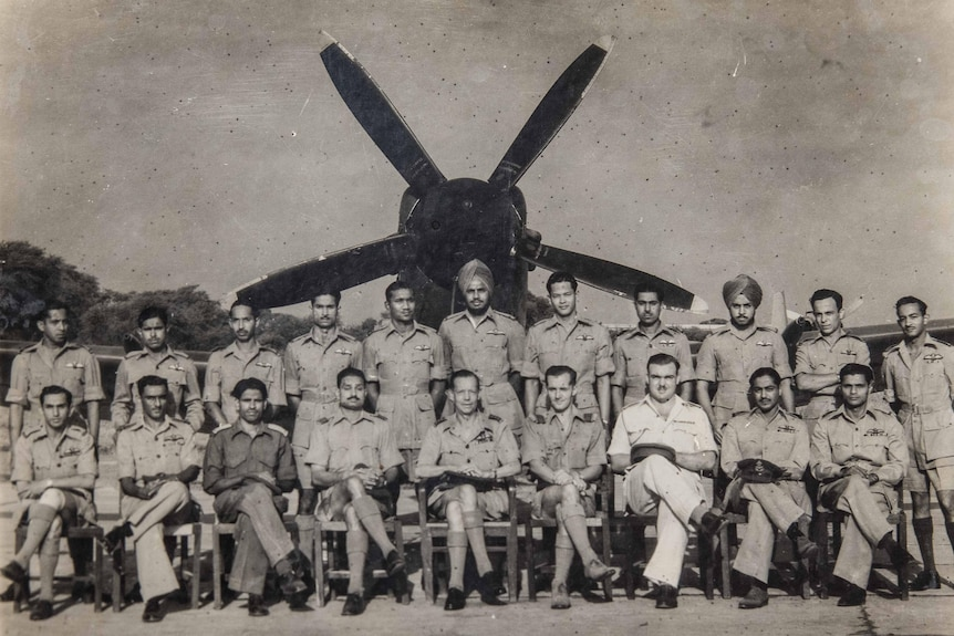 A black and white image of a group of military men in their uniforms in front of a fighter plane.