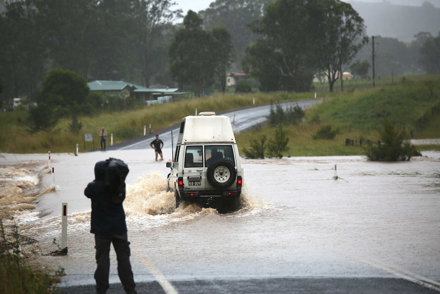 Cameraman filming 4 wheel drive vehicle driving through deep floodwaters across a road.