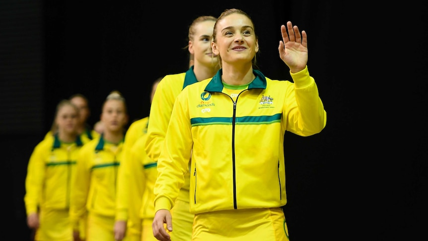 A smiling netballer walks out onto court ahead of her team before a Test match.