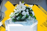 White coffin with white bouquet in a hearse.