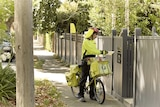 A post man delivering mail for Australia Post.