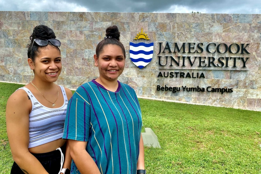 Two young Indigenous girls stands in front of a JCU sign.