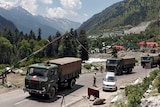 A convoy of three army trucks stops at a control point on a paved road running through a verdant valley.