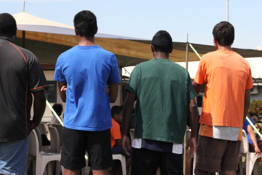 A group of young men with their backs to the camera.