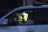 A police officer checks a driver's border pass at Coolangatta