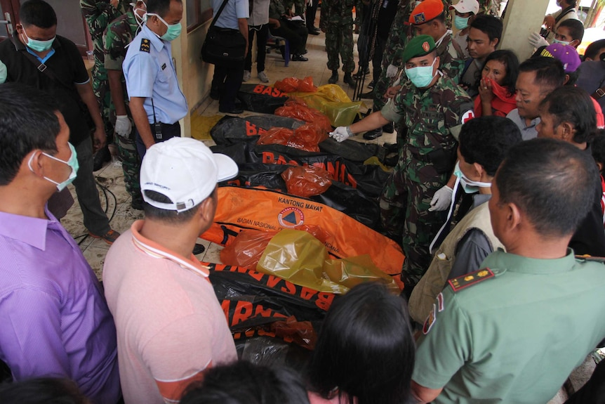 Relatives searching for missing family members gather around body bags containing victims retrieved from the crash site of an Indonesian Air Force C-130 Hercules aircraft