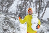 A man in the snow holding a snowman