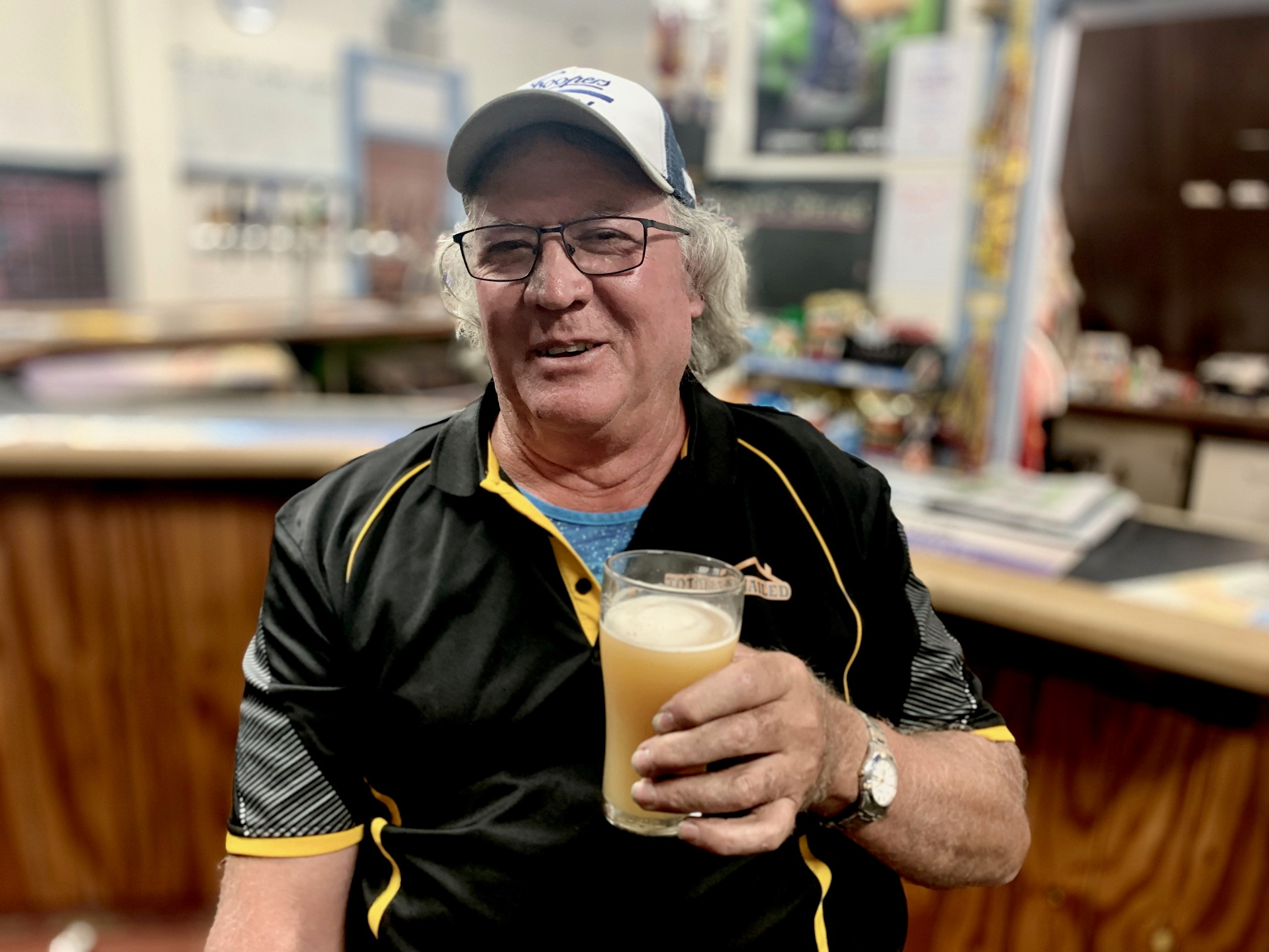 A man wearing a cap holding a beer.