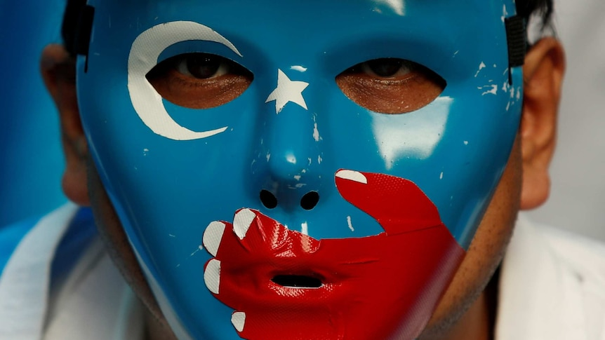 A man wears a mask with the blue East Turkistan flag on it during a protest.