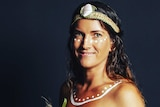 Young Aboriginal woman with white ochre dot painting under her eyes and over collarbone wearing woven grass headband with shell