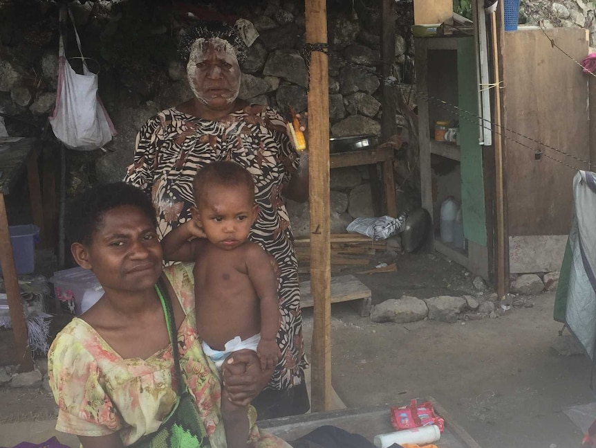 A woman sits on a bench inside a tent, holding her infant child on her hip. Another woman stands behind them.