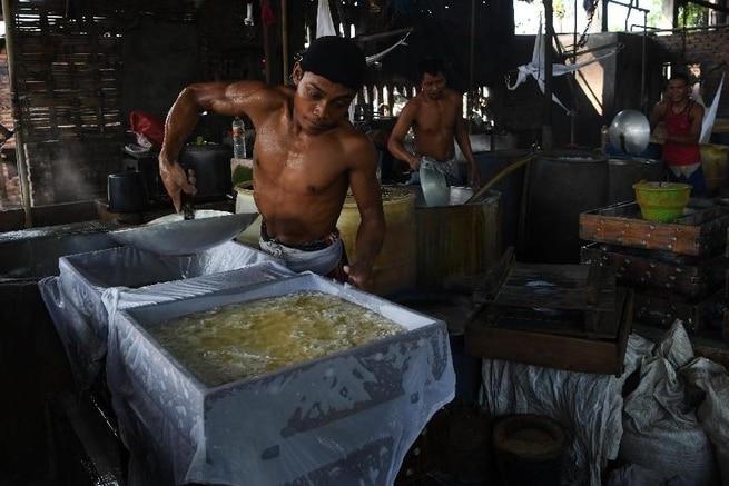 A shirtless man making tofu in a steaming tofu factory.