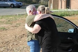 two ladies wearing masks hug next to car.