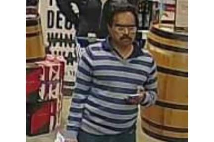 A man in a striped top holding a bottle walks through a bottle shop.