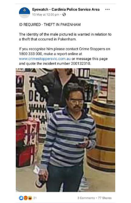 A man in a striped top walks through a bottle shop holding a bottle.