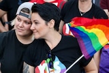 One woman with a backwards cap rests her head on another woman, who is holding a rainbow flag.