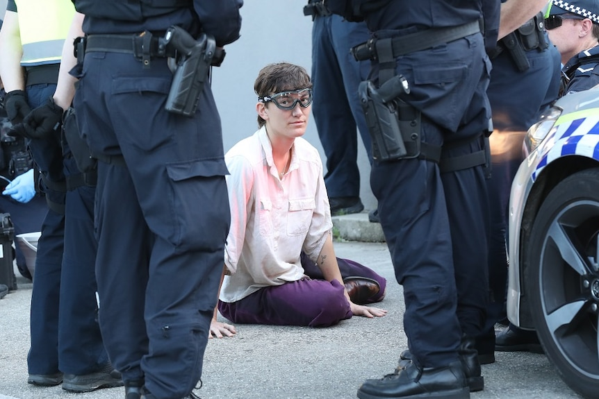 A woman wearing safety goggles sits in the middle of a driveway surrounded by police officers.