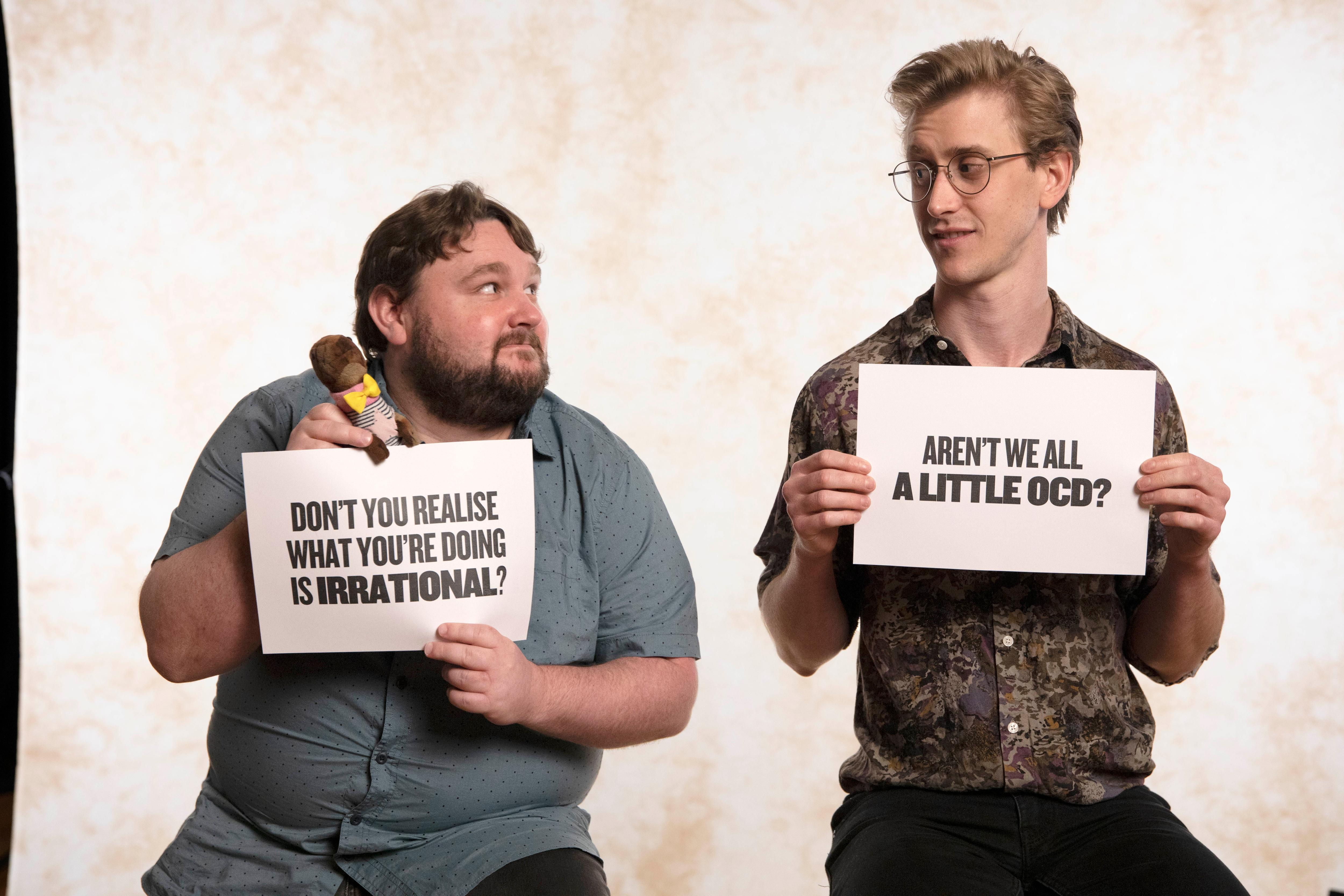 """Two men sit on stools holding signs one says """"aren't we all a little OCD?"""""""