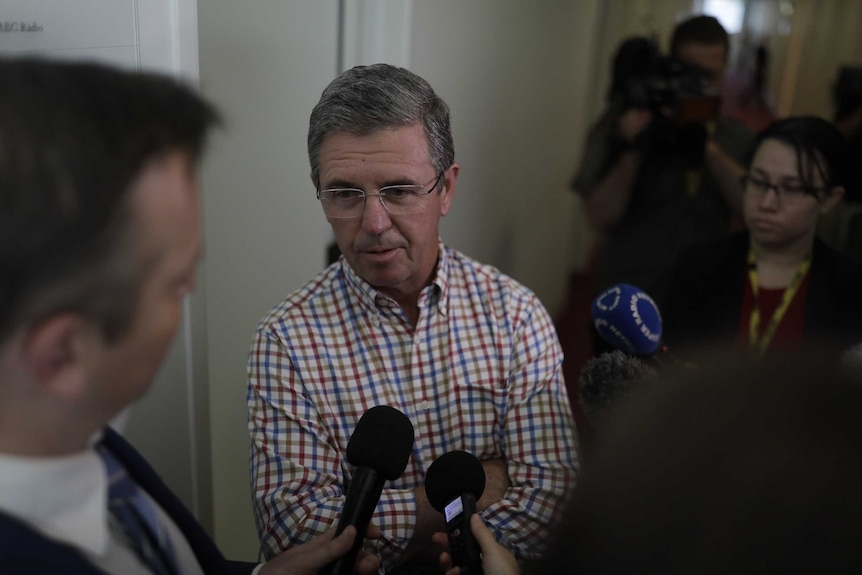 David Gillespie stands in a corridor surrounded by cameras and journalists