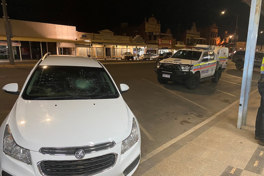 A white car which has its windscreen smashed is parked out the front of the Grand Hotel, with a police car parked nearby.