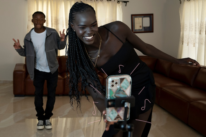 Unice and a friend dance in a living room in front of a mobile phone being held up by a stand.