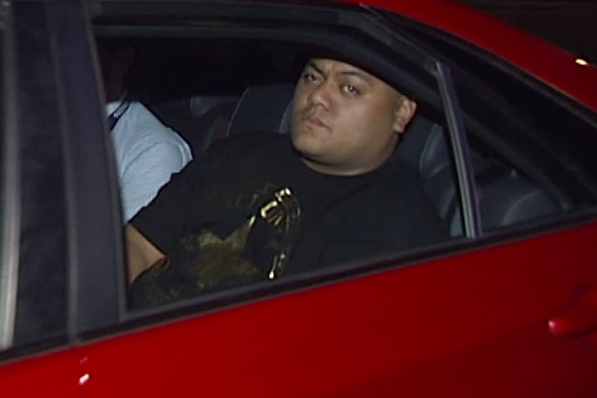Stou Daniels in the back of an unmarked police car.