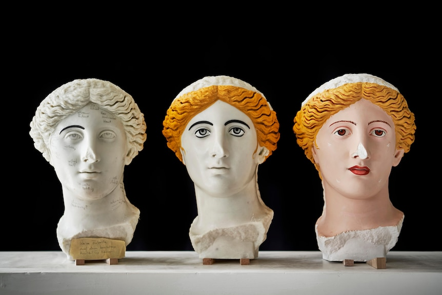 3 sculptured Roman heads, the 1st is white with one black eyebrow, the 2nd has black eyebrows + blonde hair & 3rd is in colour