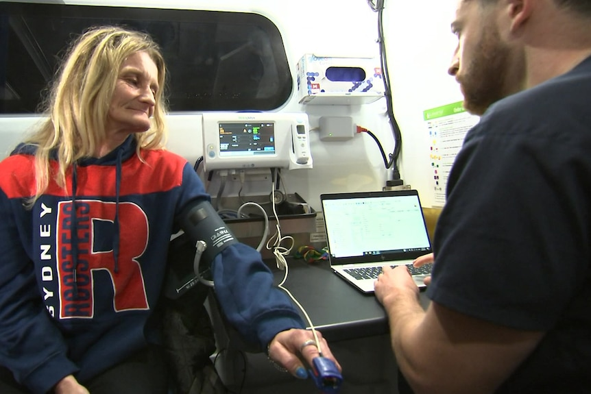 a woman with her sleeve rolled up getting her blood pressure checked