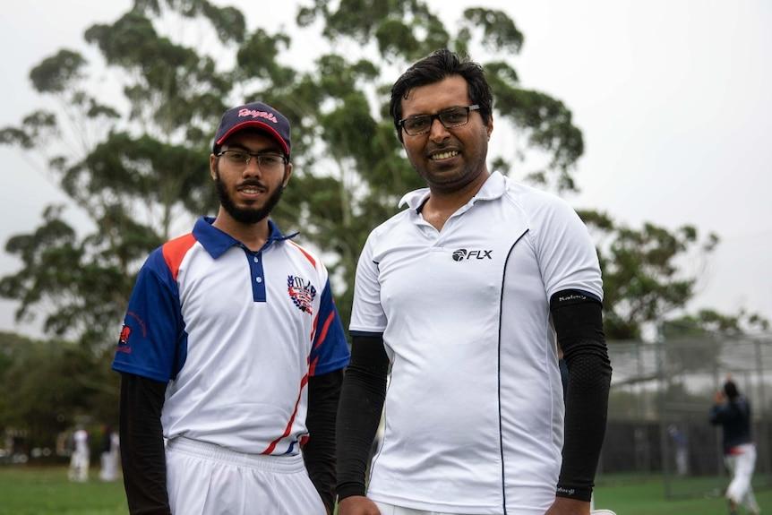 Two men dressed in cricket gear.