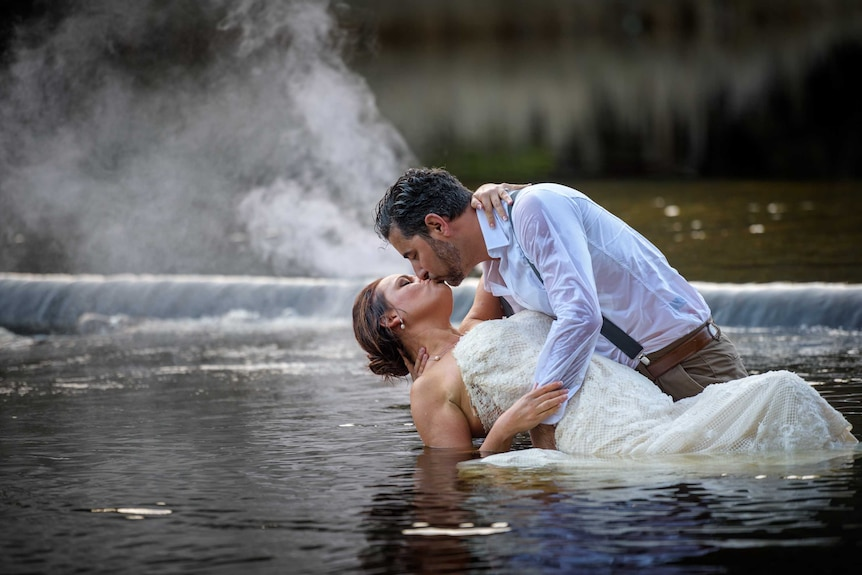 A man and a woman kiss during a photo shoot in a creek