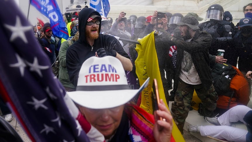 Trump supporters, including a woman wearing a Team Trump hat, try to break through a police barrier.