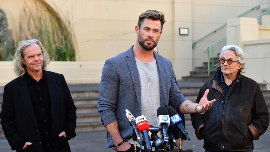 Chris Hemsworth stands at the microphone speaking, two other men stand either side of him
