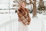 A blonde woman wears a brown fur coat over a white dress while smiling and standing on snowy field.