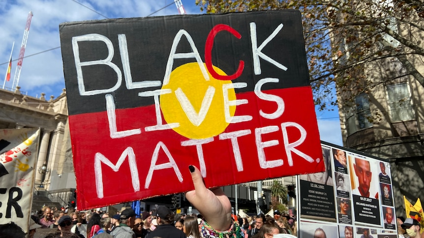 """A protester holds a """"Black Lives Matter"""" sign in front of a large crowd."""