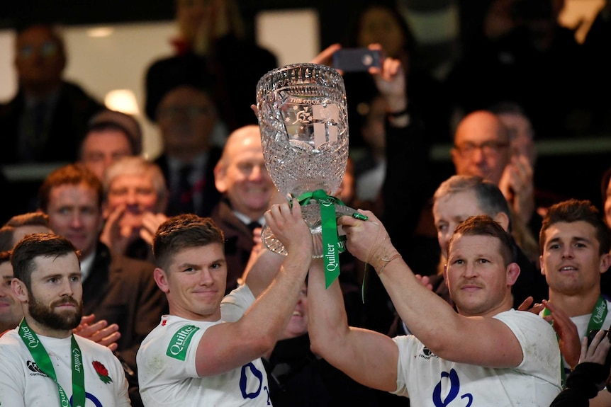 two men in white jumpers hold aloft a trophy with a crowd of people behind them
