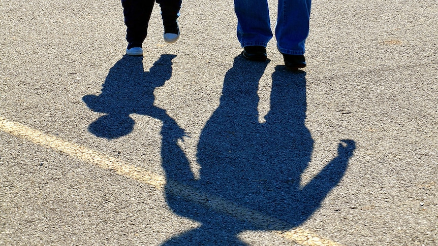 A child and adult hold hands in silhouette