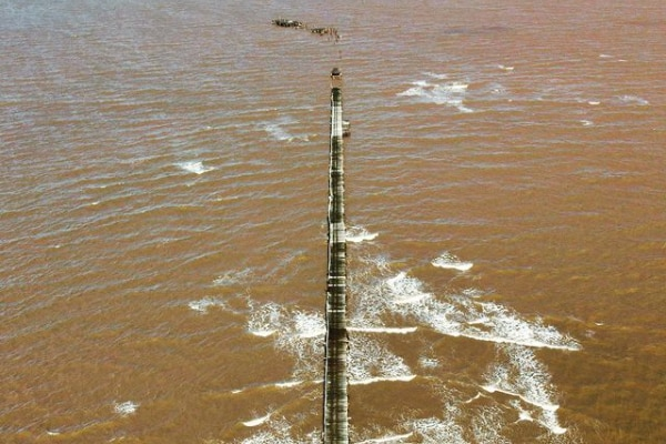 An aerial image of the severely damaged One Mile Jetty surrounded by muddy water